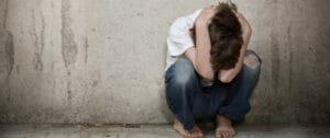 sad addicted person holding head on side of street
